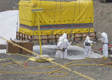 A box of transuranic waste is removed from an underground storage trench at the Hanford Site