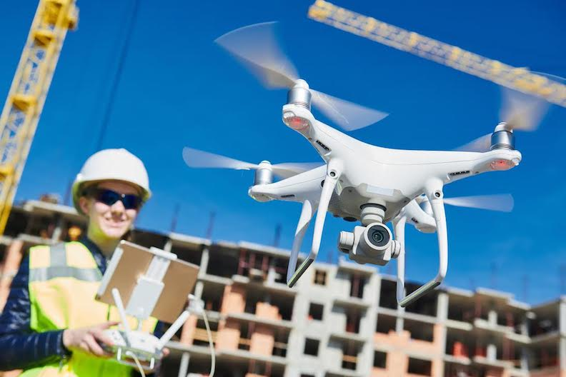 Construction worker operating drone outdoors