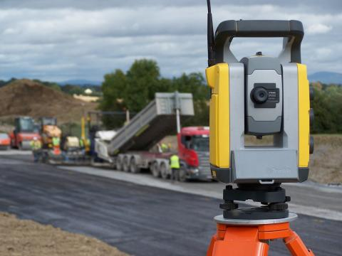 A paving project moves along under the watchful eye of a robotic total station.